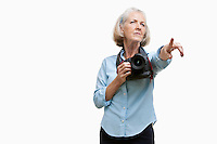 Senior female photographer with camera gesturing against white background