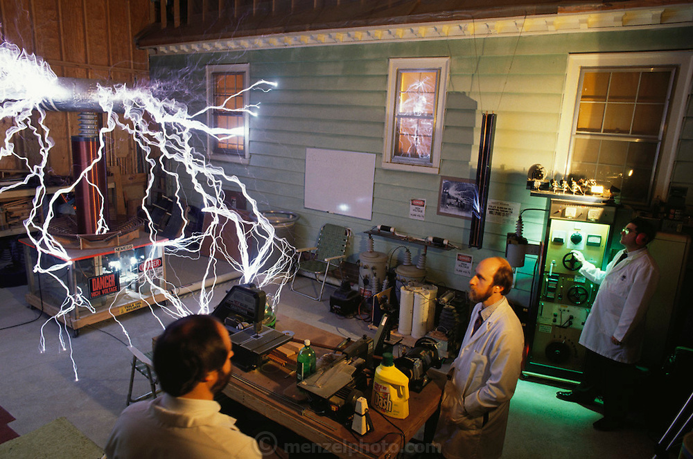 Tesla coil. Members of the Tesla Coil Builders Association seen with their largest coil nicknamed 'Nemesis'. A Tesla coil is essentially a large air-core transformer with a capacitor, named after its inventor, physicist Nikola Tesla (1856-1943). The coil is designed to give a high- voltage, high- frequency spark. Richmond, Virginia, USA. MODEL RELEASED (1992)