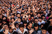Large audience of joyful vietnamese teenagers during a show in Hanoi, Vietnam, Southeast Asia