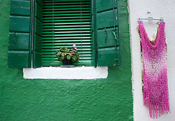 Detail of dress hanging on wall beside painted window in Burano village near Venice Italy