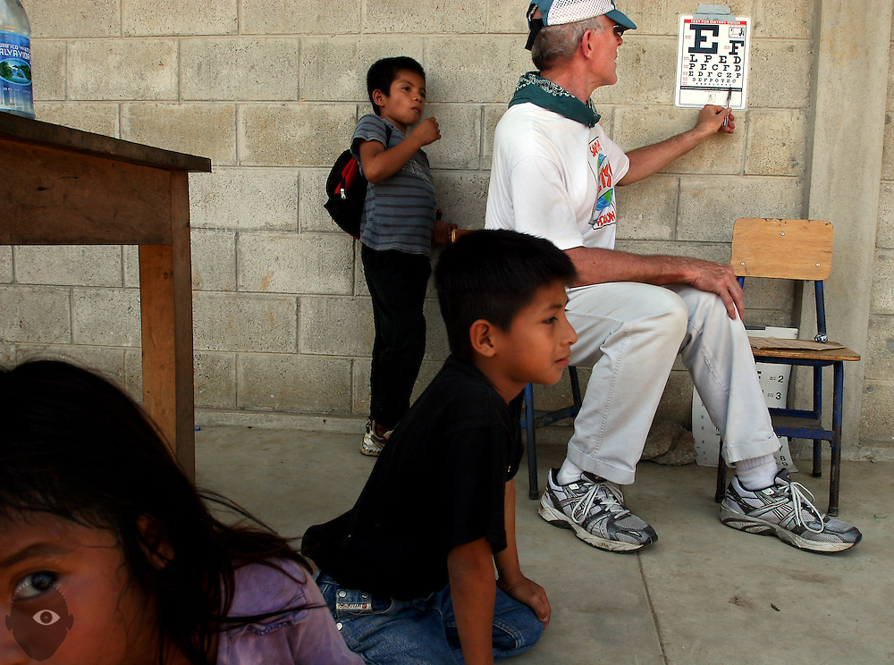 Dr. Scott Pike of Enfoque Ixcan points to an eye chart as he and his Amigos Eyecare volunteers conduct exams on elementary school students in the village of Carolina. They will spend the day there seeing hundreds of patients and dispensing many pairs of eyeglasses along with medications and advice.