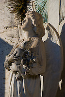Ticino, Southern Switzerland. Stone statue of an angel holding flowers in a graveyard.