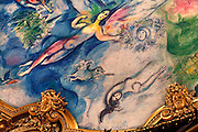 Detail of brightly coloured auditorium ceiling, 1964, by Marc Chagall (1887-1985), Palais Garnier, 1860-75, Paris, France. The ceiling, commissioned by Culture Minister Andre Malraux (1901-76), represents scenes from ballets and operas which might be performed at the Opera House. Mozart La Flute Enchantee is visible on this fragment. Picture  by Manuel Cohen.