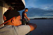 Brazilians and Colombians peer out at river backs of the Amazon during sunset aboard Avenger III. The Avenger III is a passenger ship making the twice a month journey from the frontier town of Tabatinga in the Três Fronteiras region of Northwestern Brazil, to the capital of the State of Amazonas, Manaus. It's also where the Rio Amazonas enters Brazil from its source in neighboring Peru. <br /> <br /> Carrying passengers and crew totaling almost 200 and small cargo, the ship meanders its way along the Rio Amazonas and Rio Solimoes for four days and three nights. Stopping at half a dozen or so makeshift ports en-route, the service provides a vial link for communities along the river to get products to the city and more importantly, in the absence of roads or airfields, provide a means for the sick to reach care in the city of Manaus.<br /> <br /> For those not fortunate to be accommodated in one of the two or three cabins available, home is space found for a self supplied hammock amongst the kaleidoscopic web of coloured fabrics. <br /> <br /> By the second day, negotiating a stroll from port to starboard can seem more like negotiating an assault course of tangled ropes and personal baggage deliberately piled high to protect ones personal space.<br /> <br /> Food served three times daily is adequate, a staple of soups, chicken, rice and noodles. An 'entertainment' deck on the top floor provides ample opportunity to be social engaging in card and board games with beer swilling, chain smoking locals.
