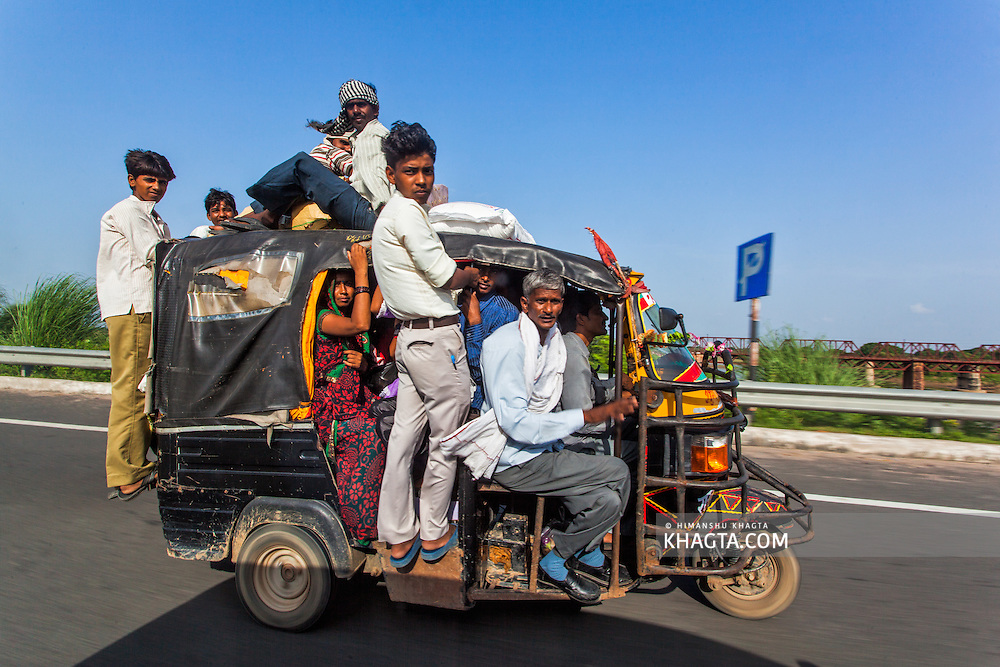 People risking their lives while being transported in an over loaded auto rickshaw violating all safety norms on the national highway.