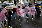 Visitors to the capital wearing identical plastic macs endure heavy rainfall on an autumn afternoon in Trafalgar Square, on 24th October 2019, in Westminster, London, England.