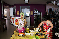 """ROME, ITALY - 3 JULY 2016: (L-R) Gipsy Queens members Codruta Balteau (24) and Darmaz Florentina (33) prepare typical Roma dishes for their food stand at the iFest, an alternative music festival, here in the Astra 19 social center in Rome, Italy, on July 3rd 2016.<br /> <br /> The Gipsy Queens are a travelling catering business founded by Roma women in Rome.<br /> <br /> In 2015 Arci Solidarietà, an independent association for the promotion of social development, launched the """"Tavolo delle donne rom"""" (Round table of Roma women) to both incentivise the process of integration of Roma in the city of Rome and to strengthen the Roma women's self-esteem in the context of a culture tied to patriarchal models. The """"Gipsy Queens"""" project was founded by ten Roma women in July 2015 after an event organised together with Arci Solidarietà in the Candoni Roma camp in the Magliana, a neighbourhood in the South-West periphery of Rome, during which people were invited to dance and eat Roma cuisine. The goal of the Gipsy Queen travelling catering business is to support equal opportunities and female entrepreneurship among Roma women, who are often relegated to the roles of wives and mothers."""