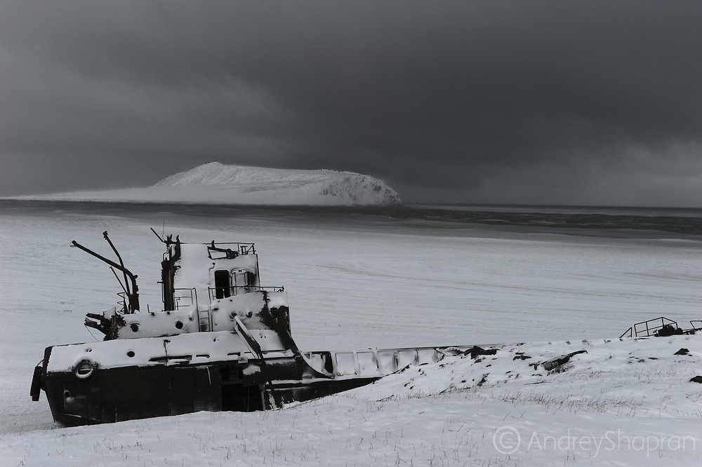 A wrecked ship in the heavy snowstorm on the Arctic coast of Chukotka in the Schmidt Cape settlement, Russia