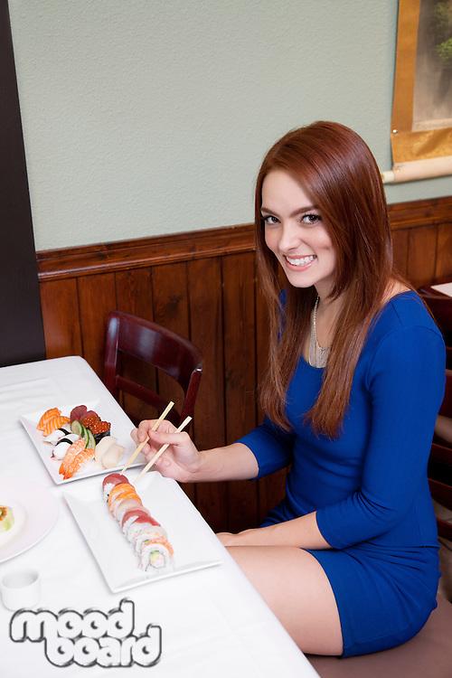 Beautiful young woman having sushi in restaurant