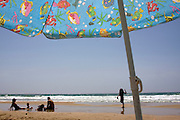 Summer Beach scene. An out of focus family with young children on the waterfront a colourful parasol in the foreground