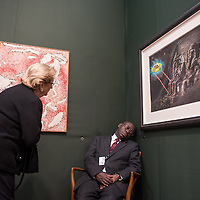 London, UK - 15 October 2014: a visitor takes a closer look to the Sleeping Guard by Christoph Buchel  performs at the Hauser & Wirth stand during the first day of Frieze Art Fair and Frieze Masters in Regent's Park.