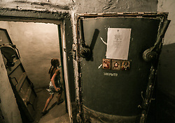 Local girl runs through the door to the shelter with Orthodox icons for hiding in the shelter in Ilovaysk (50km from Donetsk), Ukraine, 14 August 2014. Town Ilovaysk was destroyed by Ukranian army's shelling during last two weeks. More than two thousand people all night and day live in their shelter. They haven't water, <br />