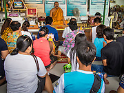 "21 JULY 2013 - BANGKOK, THAILAND:   A family makes merit and presents a monk with alms at Wat Mahabut on the first day of Vassa, the three-month annual retreat observed by Theravada monks and nuns. On the first day of Vassa (or Buddhist Lent) many Buddhists visit their temples to ""make merit."" During Vassa, monks and nuns remain inside monasteries and temple grounds, devoting their time to intensive meditation and study. Laypeople support the monastic sangha by bringing food, candles and other offerings to temples. Laypeople also often observe Vassa by giving up something, such as smoking or eating meat. For this reason, westerners sometimes call Vassa the ""Buddhist Lent.""       PHOTO BY JACK KURTZ"