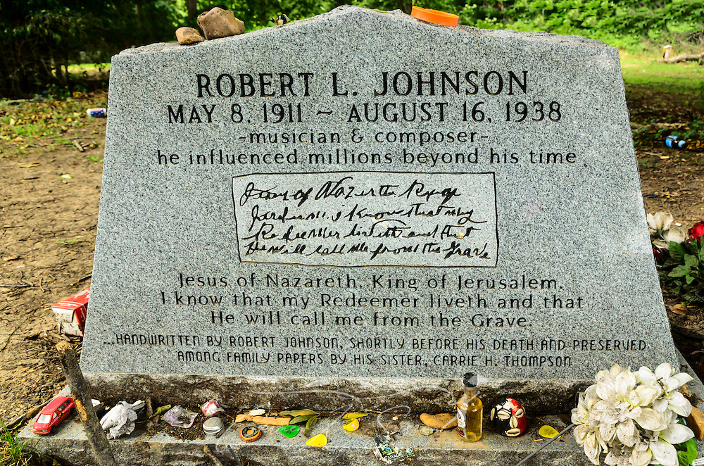 "Tokens from fans of legendary blues musician Robert Johnson litter what is believed to be his gravesite at Little Zion Missionary Baptist Church in Greenwood, Miss. Some of the items include a Japanese ""Hello Kitty"" doll, a bracelet inscribed in French, guitar picks, and liquor bottles.   (Photo by Carmen K. Sisson)"