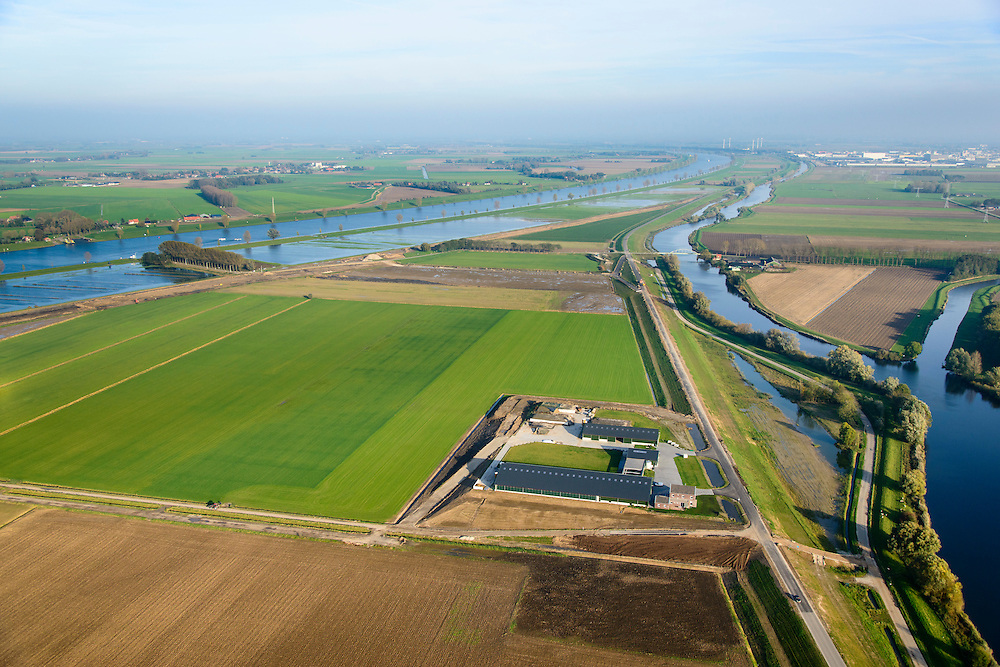 Nederland, Brabant, Gemeente Waspik, 28-10-2014; Overdiepsche polder: in het kader van het programma 'Ruimte voor de Rivier' (bescherming tegen hoogwater door rivierverruiming), is de dijk langs de Bergsche Maas (links in beeld) verlaagd. Bij hoogwater kan de Overdiepse polder overstromen. De boerderijen in de polder zijn gesloopt en verplaatst naar de dijk van het Oude Maasje. De nieuwe boerderijen met bijgebouwen staan op terpen.<br /> Depoldering of Overdiep Polder, farms are relocated and built on mounds. This makes it possible for the river to overflow the polder in case of heigh waters.<br /> luchtfoto (toeslag op standard tarieven);<br /> aerial photo (additional fee required);<br /> copyright foto/photo Siebe Swart