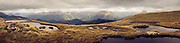 Panoramic of alpine tarns amongst the golden tussock in Fiordland National Park, New Zealand.