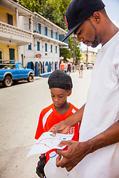Junior Rodgers, left, and Kai Frett look over the map of the Garden Street neighborhood and walking tour.  Residents and volunteers gather for the Garden Street neighborhood cleanup and block Party hosted by E's Garden and Things, Long Path/Garden Street Community Association, and the Economic Development Authority's Enterprise and Commerical Zone Commission.  St. Thomas, USVI.  5 September 2015.  © Aisha-Zakiya Boyd
