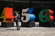 A city worker uses his smartphone by an art installation entitled 'One Through Zero (The Ten Numbers)' by American pop artist Robert Indiana (b 1928), in Lime Street, City of London, the capital's Square Mile, and its financial heart.