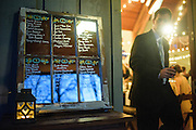 Annapolis, Maryland - April 18, 2015: A wedding guest walks past the seating arrangements list -- names are written on a mirrors inside a repurposed window. Stephanie Shearer Cate and Winston Bao Lord wed at their friends Jeff and Marry Zients' house in Annapolis, Maryland Saturday April 18, 2015. <br /> <br /> <br /> <br /> CREDIT: Matt Roth for The New York Times<br /> Assignment ID: 30173318A