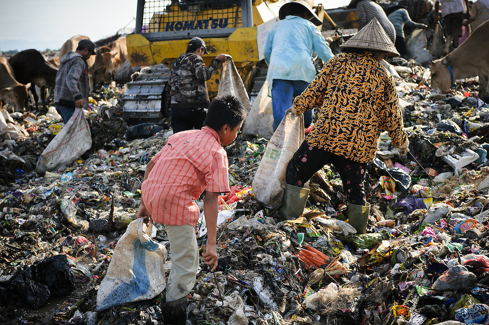 Taupik, 14, walking behind a bulldozer on the 'Trash mountain', Makassar, Sulawesi, Indonesia.  Many of the pickers follow the bulldozers as they move newly dumped waste, uncovering plastic and metal for recycling in the process.