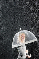 Smiling businesswoman Standing Under Umbrella during rain