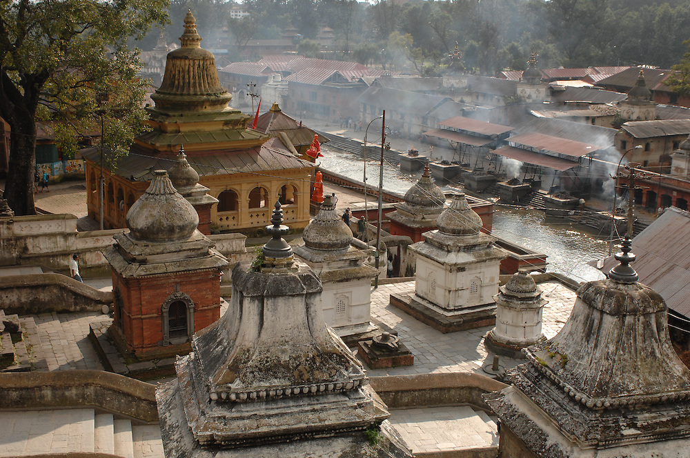 A view of small temples and shrines with crematory smoke in the background at Pashupatinath Temple, in Kathmandu, Nepal.