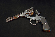 Webley Mark VI revolver with burst barrel and six visible bullets.