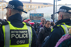 "St Pancras, London, January 16th 2016. Dozens of protesters hold an ""emergency demonstration and die-in"" as France prepares to bulldoze the Jungle Camp at Calais. PICTURED: Bemused travelers make their way into the St Pancras Eurostar terminal, through the protest and police lines blocking entry to the demonstrators. ///FOR LICENCING CONTACT: paul@pauldaveycreative.co.uk TEL:+44 (0) 7966 016 296 or +44 (0) 20 8969 6875. ©2016 Paul R Davey. All rights reserved."