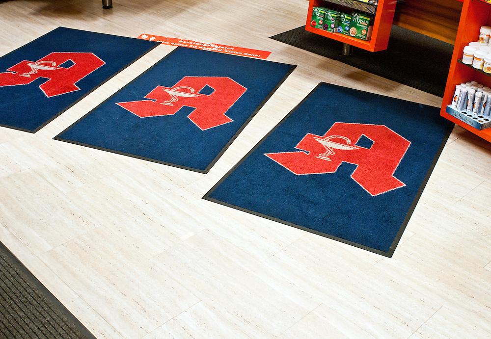 Drei Fussmatten im  mit dem A für Apotheke  auf dem Boden liegend im Ladenlokal einer Apotheke         