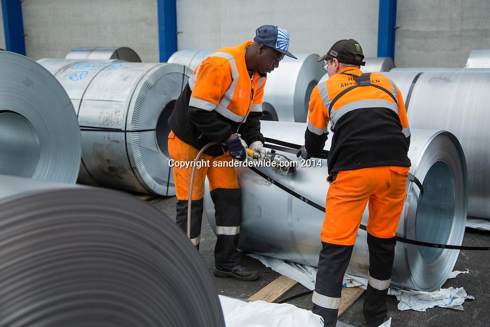 Two harbor workers working on a stock of metal rolls at Van Moerk group  in the port of Antwerp,
