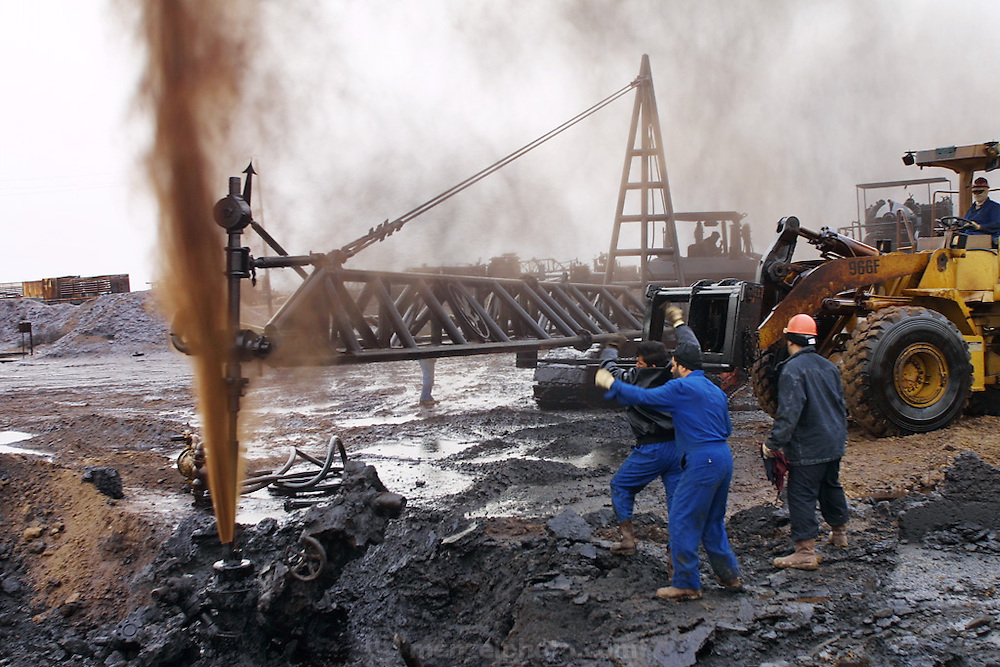 "Firefighters from the KWWK (Kuwait Wild Well Killers) attempt to kill an oil fire in the Rumaila field by guiding a ""stinger"" that will pump drilling mud into the damaged well. A ""stinger"" is a tapered pipe on the end of a long steel boom controlled by a bulldozer. Drilling mud, under high pressure, is pumped through the stinger into the well, stopping the flow of oil and gas. A sudden wind shift after a sandstorm caused the oil to blow back on the workers and equipment, causing a very dangerous situation because the oil and gas could have easily ignited. The Rumaila field is one of Iraq's biggest oil fields with five billion barrels in reserve. Many of the wells are 10,000 feet deep and produce huge volumes of oil and gas under tremendous pressure, which makes capping them very difficult and dangerous. This well is of relatively low volume. Rumaila is also spelled Rumeilah.."