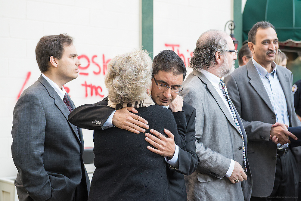 Christy Brown, founder of the Center for Interfaith Realtions, hugs Dr. Muhammad Babar, a member of the congregation and spokesman for the Louisville Islamic Center on River Road, after a press conference about graffiti sprayed on the mosque Wednesday night. Sep. 17, 2015