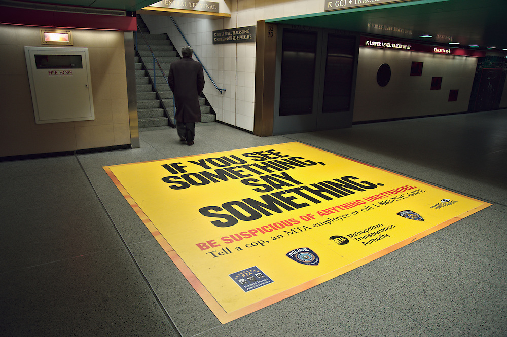 "Man in Grand Central Terminal walking with back to sign on floor reading ""If you see something, say something"", urging people to report suspicious activity."