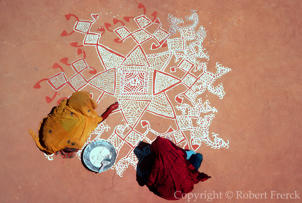 INDIA, FAMILY women laying decoration of colored pigments on floor of family compound in preparation for a wedding ceremony