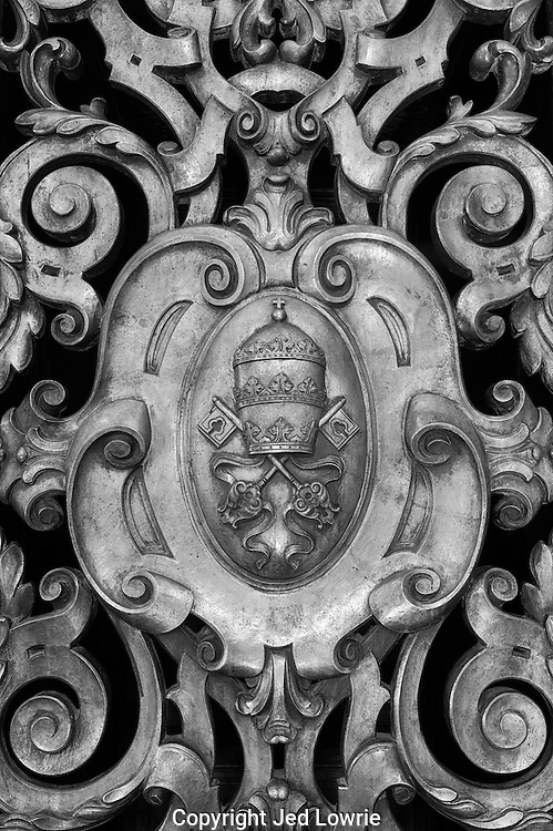 An intricate iron gate with the crest of The Pope makes for nice image. It is visually consuming with all of the carved details.