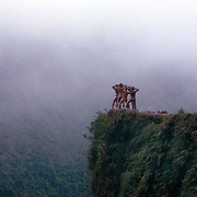 Mountain Biking on Death Road, Bolivia...A tour group of young British and Australian tourists celebrate their success of completing the 64 kilometer journey mountain biking down the infamous narrow dirt road by posing nude for a photograph on a landmark bend of the road... The road was built in the 1930's during the Chaco War by Paraguayan prisoners to connect the Amazon rainforest region of Northern Bolivia to it's capital City La Paz. One estimate is that 200 to 300 travelers were killed yearly along the road. On 24 July 1983, a bus veered off the Yungas Road and into a canyon, killing more than 100 passengers in what is said to be Bolivia's worst road accident..A new stretch of the La Paz-Coroico highroad was opened in 2006 to bypass the notorious stretch known as death road..The danger of the road has now made it a popular tourist destination starting in the 1990's and drawing thrill-seekers and mountain bike enthusiasts who ride on the 64km mainly downhill stretch from La Cumbre, a 4,700 meter peak to Yolosa, a decent of 3600 meter's (11,800 feet). The journey includes breathtaking views of snow covered peaks and towering cliffs and starts along modern asphalted road before entering the jungle itself and the most dangerous and notorious part of the ride. The infamous narrow dirt road, most of the road no wider than 3.2 meter's, is cut into the side of the mountain with sheer drops to the left of up to 600 meter's with virtually no safety rails on the winding steep decent..There are now many tour operators catering to this activity, providing information, guides, transport and equipment. Nevertheless, the Yungas Road remains dangerous. At least 13 of these cyclists died on the ride since 1998, the latest A 28-year-old Israeli traveler was killed in April 2010  the group of cyclists arrived at a heavily foggy area. The woman got separated from the group, and fell into a chasm which resulted in her death. Despite this the road remains a daily attraction for tour