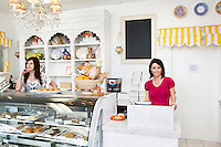 Portrait of a happy mid adult woman standing at checkout counter with coworker in cake shop
