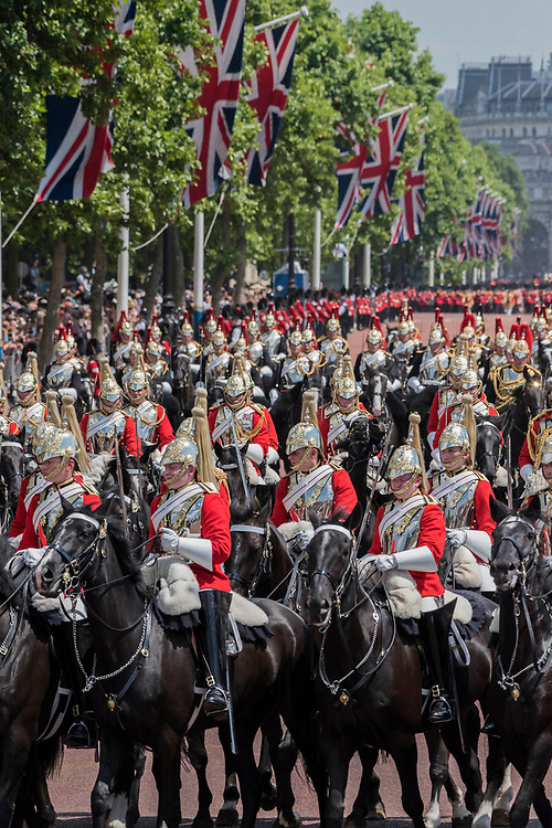 """The Household Cavalry return to Buckinham Palace down the Mall - Trooping the Colour by the Irish Guards on the Queen's Birthday Parade. The Queen's Colour is """"Trooped"""" in front of Her Majesty The Queen and all the Royal Colonels.  His Royal Highness The Duke of Cambridge takes the Colonel's Review for the first time on Horse Guards Parade riding his horse Wellesley. The Irish Guards are led out by their famous wolfhound mascot Domhnall and more than one thousand Household Division soldiers perform their ceremonial duty. The Soldiers will parade in the traditional ceremonial uniforms of the Household Cavalry, Royal Horse Artillery, and Foot Guards. They are accompanied by the Household Division Bands & Corps of Drums. London 17th June 2017."""