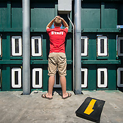 Scoreboard attendant, 16 year old-Carl Steffens,  watches the game through a whole in the scoreboard in centerfield at Nat Bailey Stadium, home of the Vancouver Canadians.