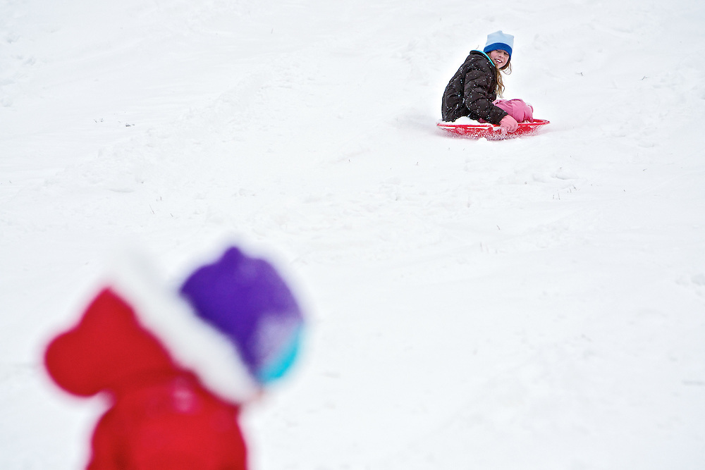 Kelsey Sonius, 10, speeds to the bottom of Cherry Hill on her sled Tuesday another sledder makes their way up the popular sledding hill in Coeur d'Alene.