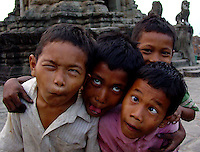 Four young boys at the Angkor Wat ruins complex in Siem Reap make crazy faces.