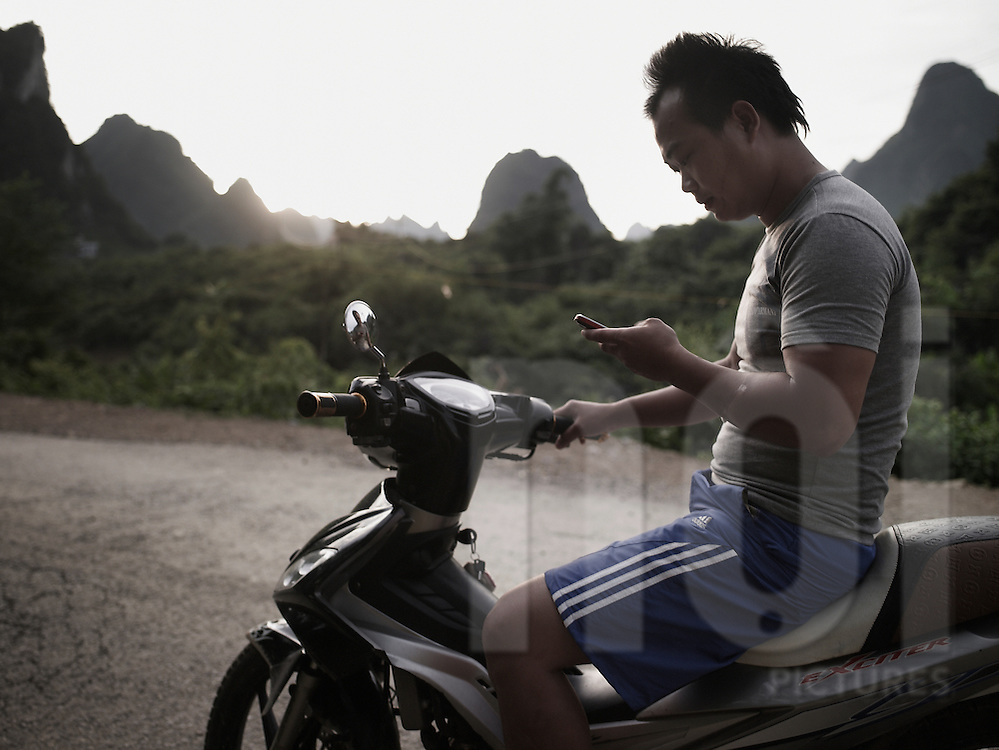 A vietnamese man sits on his motorbike and types out on his cell phone. Cao Bang province, Vietnam, Asia.