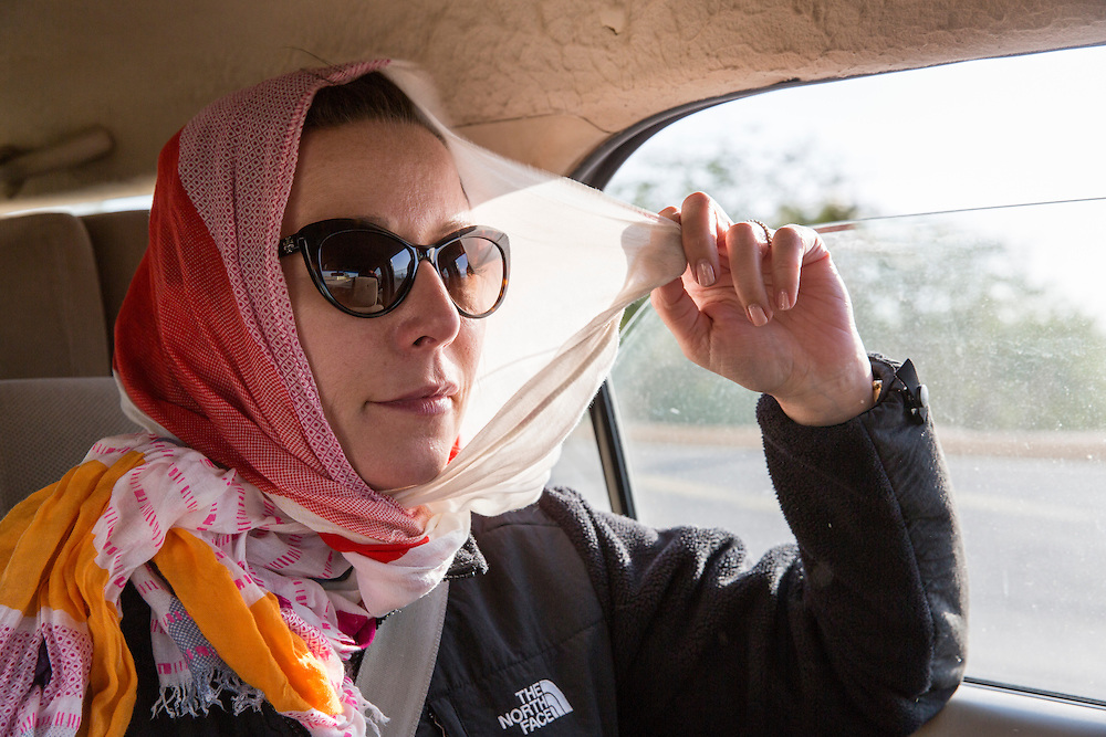 Jordan, Wadi Rum, American woman uses scarf to shade herself from scorching desert run while riding in back of taxi