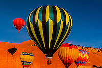 Hot air balloons flying during the Red Rock Balloon Rally, Red Rock State Park, near Gallup, New Mexico USA.