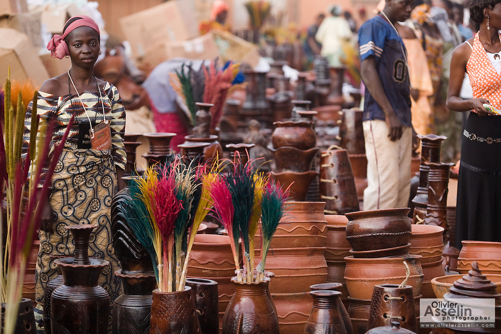 A woman selling pottery stands among her wares at the 22nd Salon International de l'Artisanat de Ouagadougou (SIAO) in Ouagadougou, Burkina Faso on Saturday November 1, 2008.