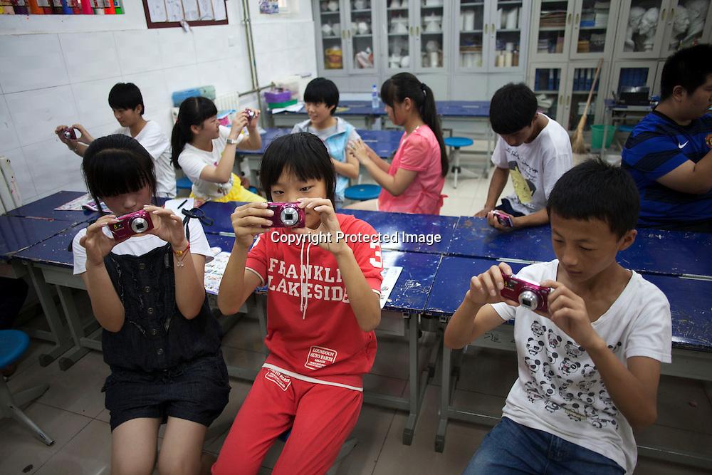 BEIJING, JULY,12-14,2013 : Teilnehmer eines Foto Workshops in der CAOCHANGDI MITTELSCHULE arbeiten mit ihren Kameras im Klassenraum .