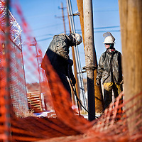 010313       Cable Hoover<br /> <br /> Contractors Max Holmes, right, and Michael Julian use a hydro-vac machine to dig a trench for a new electrical conduit near Gallup's west side Thursday.