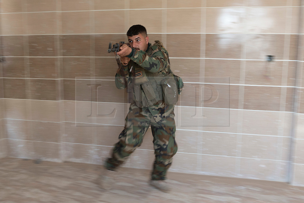 © Licensed to London News Pictures. 09/03/2015. Erbil, Iraq. Kurdish peshmerga fighters practice clearing rooms in a building during an urban warfare training session run by German soldiers at a partially finished housing estate near Erbil, Iraq. <br /> <br /> The training is part of a four week platoon level infantry training package run by coalition forces aimed at improving the efficiency of the Iraqi Security Forces. Photo credit: Matt Cetti-Roberts/LNP