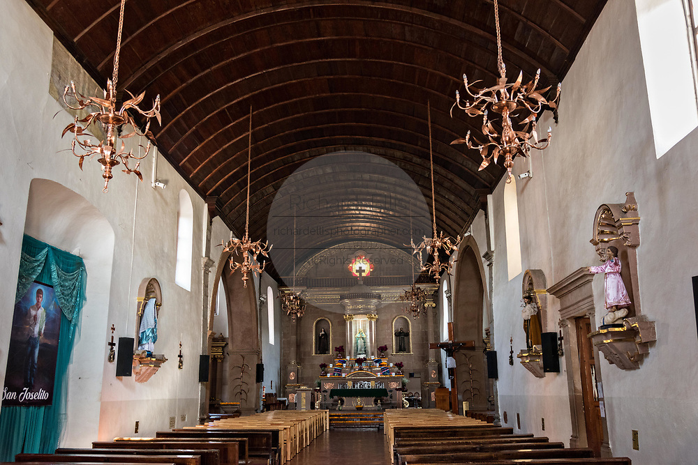Interior of the Templo de Nuestra Señora del Sagrario church with a barrel wooden ceiling and copper chandeliers in Santa Clara del Cobre, Michoacan, Mexico.