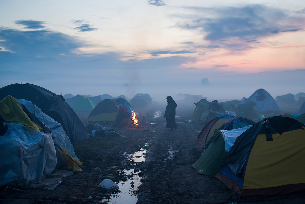 A woman walks between tents at dawn at a refugee camp on the Macedonian (FYROM) border on March 11, 2016 in Idomeni, Greece.